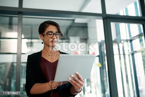 Cropped shot of an attractive young businesswoman standing alone in her office and working on a tablet
