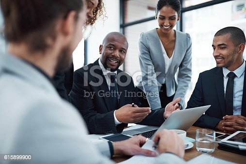 Shot of a group of businesspeople discussing something on a laptop