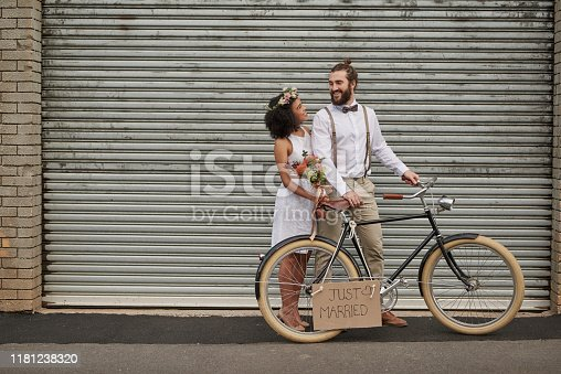 Shot of a newly married young couple taking their bicycle through the city on their wedding day