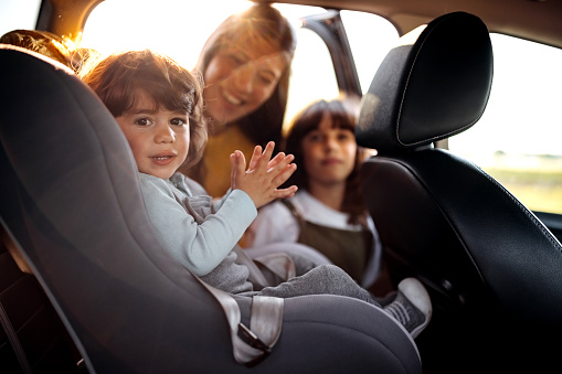 Mother tightening seatbelt for kind on back seat
