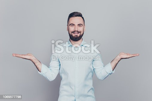 istock You have double alternative! Close up studio photo portrait of handsome glad fashionable cool cheerful excited human him he has direction tip proposal hold on palms isolated grey background copy space 1069577798