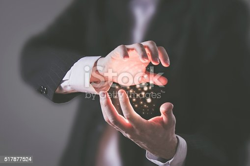 Concept - Businesssman using his inner power and concentrating glowing energy particles between his hands