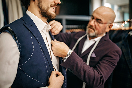 Senior salesman measuring length of sleeve for customer