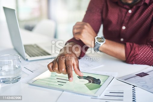 Closeup shot of an unrecognizable man analyzing statistics on a digital tablet in an office