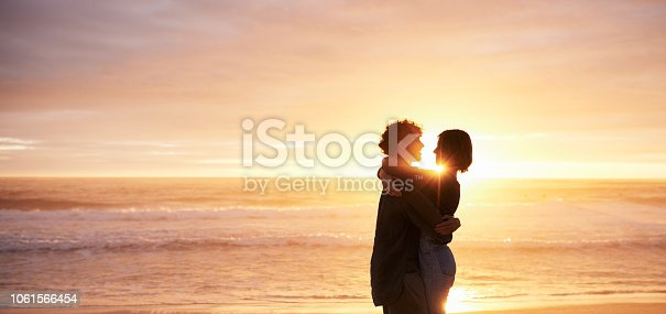 Shot of a young couple sharing an affectionate moment on the beach at sunset