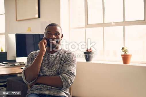 Shot of a young businessman using a mobile phone at his desk in a modern office