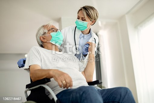 Below view of female doctor holding hands with senior man in wheelchair while visiting him at home during coronavirus lockdown.