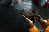 Staying connected on the move. African American woman in restaurant using smart phone. Focus on hand. Close up. African american person holding a tactile mobile smartphone - Black people.