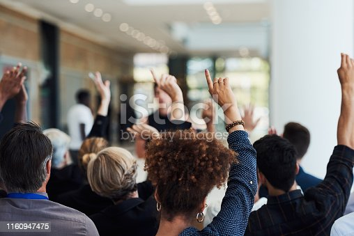 Shot of a group of businesspeople raising their hands to ask questions during a conference