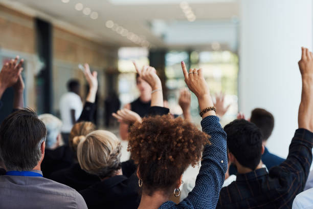 You learn through asking Shot of a group of businesspeople raising their hands to ask questions during a conference attending stock pictures, royalty-free photos & images