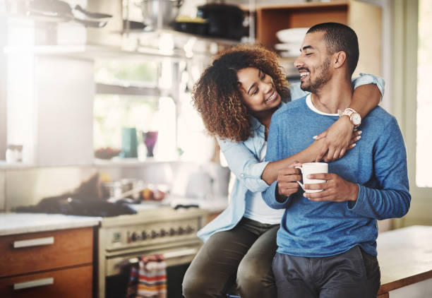 You make me a happy man Shot of a happy young couple relaxing in the kitchen in the at home face to face stock pictures, royalty-free photos & images