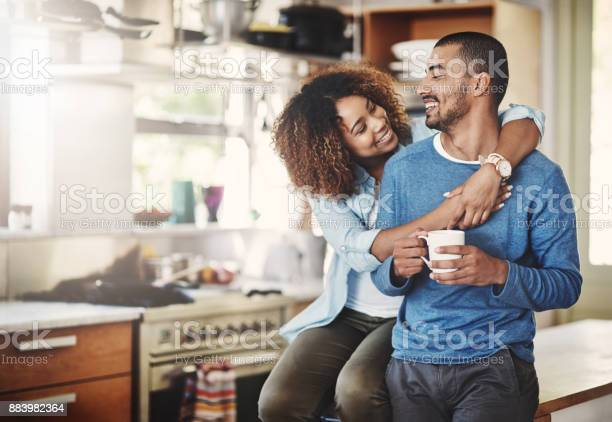 Shot of a happy young couple relaxing in the kitchen in the at home