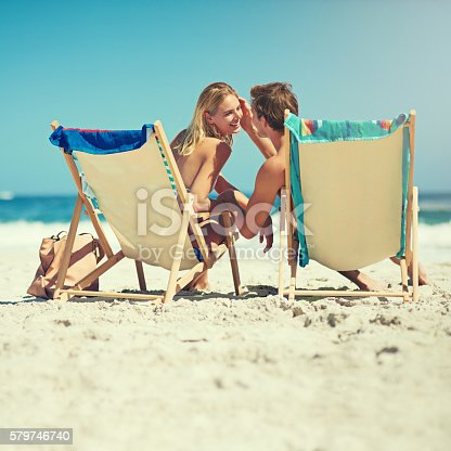 Rearview shot of a young couple sitting on loungers at the beach