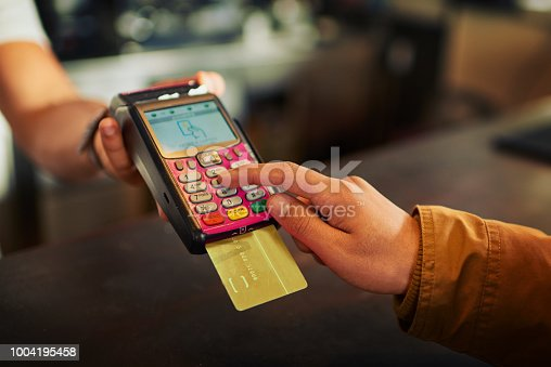 Closeup of an unrecognizable person paying their bill with a card machine inside of a restaurant during the day