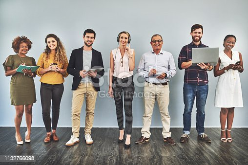 Shot of a group of business people using their smart devices while standing against a wall