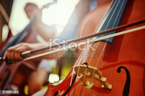 Cropped shot of an unrecognizable woman playing a cello outdoors