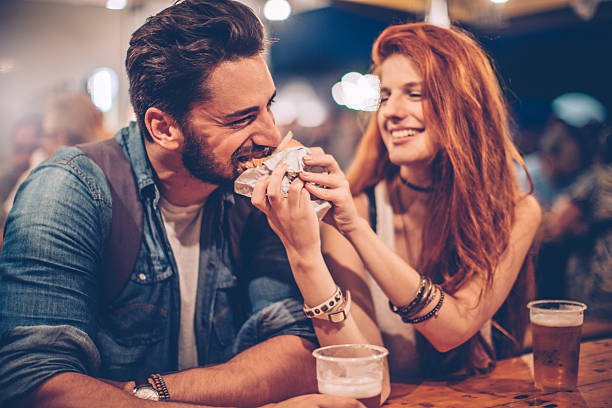 You must try this burger A young couple having snack and drink at an outdoors music festival. They drink  for nice time they spend together. date night romance stock pictures, royalty-free photos & images