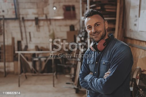 Portrait of Carpenter on His Workplace in Carpentry Workshop Looking at Camera. Profession, Carpentry, Woodwork and People Concept. Small Business Owner