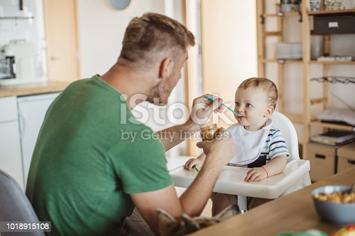 Father feeding young son, they are at kitchen table