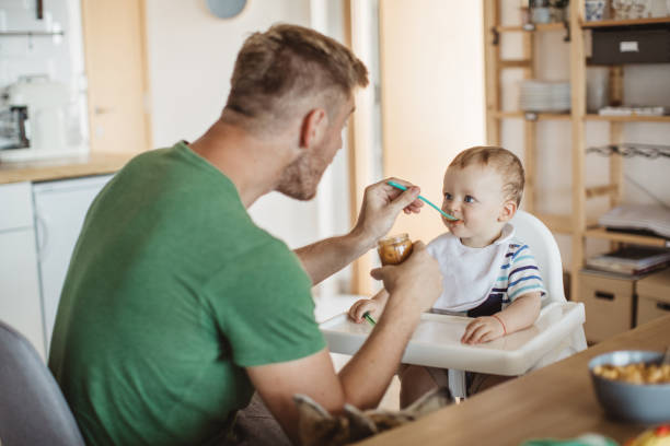 You need to eat to get big and strong Father feeding young son, they are at kitchen table stay at home father stock pictures, royalty-free photos & images