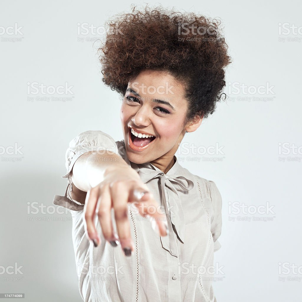 You! Portrait of beautiful teenaged afro girl pointing with index finger and laughing at the camera. Studio shot, grey background. 18-19 Years Stock Photo