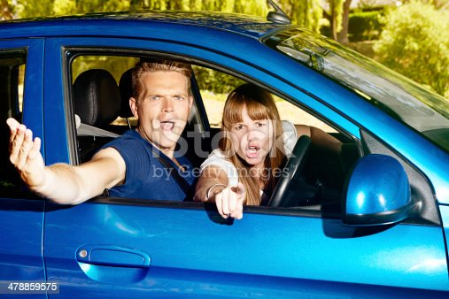 475395935istockphoto You roadhog! Young couple in car gesture angrily at someone 478859575