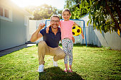 Portrait of a happy father and daughter playing with a football in the backyard