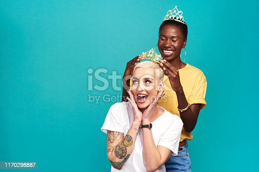 Studio shot of a young woman putting a crown on her friend against a turquoise background