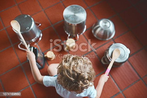 High angle shot of an unrecognizable little boy playing with pots in the kitchen