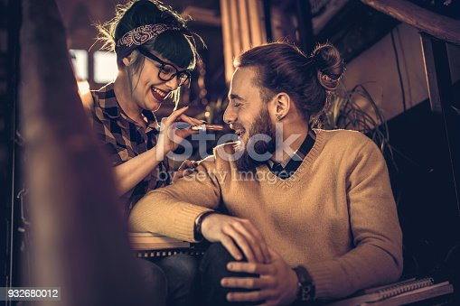 Happy college couple relaxing on staircase in library while woman is feeding her boyfriend with chocolate.