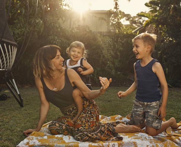 you wanna get on too? - mãe criança brincar relva efeito de refração de luz imagens e fotografias de stock