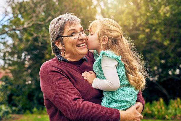 You will always be Granny's little girl Shot of a granddaughter kissing her grandmother on the cheek outside kissinghand stock pictures, royalty-free photos & images