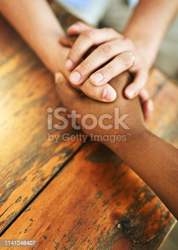 Shot of an unrecognizable person holding another person's hand in comfort outside during the day