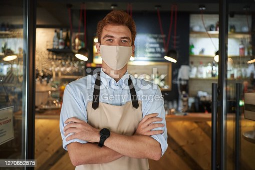 Redhead male coffee shop worker wearing protective face mask and standing on a doorway excited and ready for the new customers