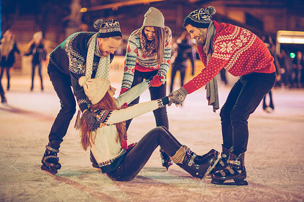 You will learn it some day Friends having so much fun while ice skating.  Wearing warm clothing. City is decorated with christmas lights. ice skating stock pictures, royalty-free photos & images