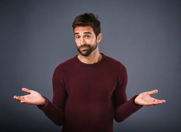 You win some, you lose some Studio shot of a handsome young man gesturing in indifference against a gray background shrugging stock pictures, royalty-free photos & images
