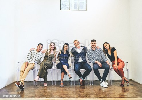 Portrait of a group of businesspeople sitting together on chairs against a white wall