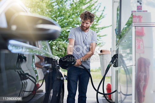 Cropped shot of a handsome young man refuelling his car at a gas station