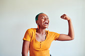 Shot of a beautiful young woman flexing her muscles against a white background