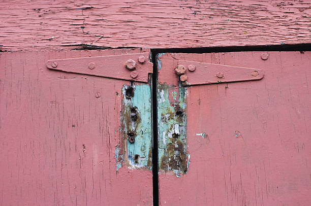 old hinges on pink paint dilapidated doors - whiteway stock photos and pictures