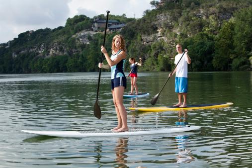 Youg adults paddleboarding stand up paddling