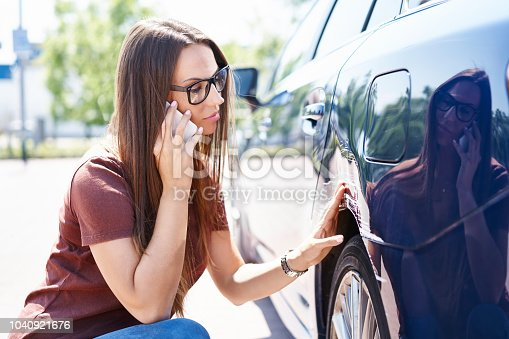 istock Yougn woman inspecting her scratched car and calling insurance agent 1040921676