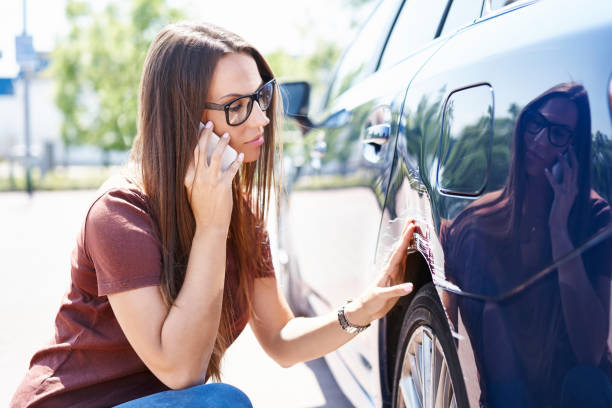 Yougn woman inspecting her scratched car and calling insurance agent stock photo