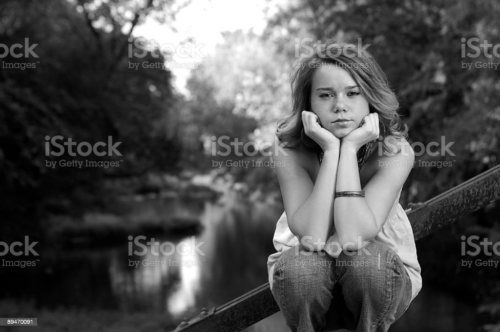 Youing girl sitting on bridge royalty-free stock photo
