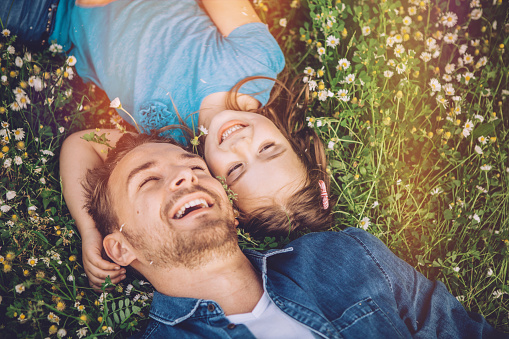 Father and his cute daughter having fun outdoors in a meadow. Lying on green grass and daisy flowers, embracing. Caucasian, blond hair.