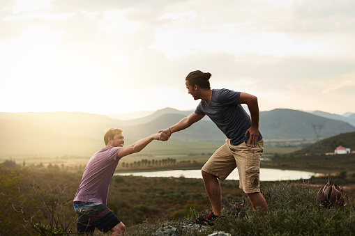 Shot of a friendly young hiker helping his friend climb onto a rock on a mountain trail