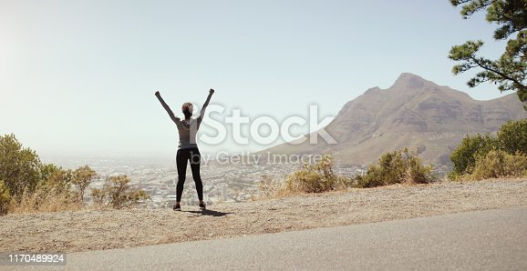 Rearview shot of a sporty young woman celebrating with her arms raised while exercising outdoors