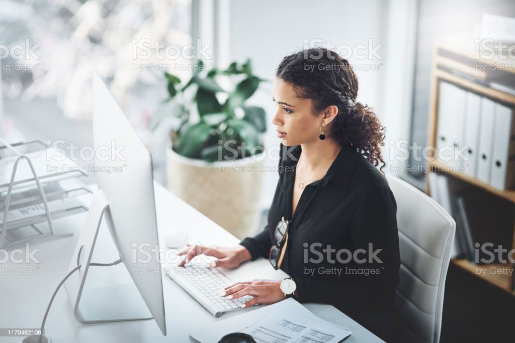 You'll succeed as long as you stay focused Shot of a young businesswoman working on a computer in an office 20-29 Years Stock Photo