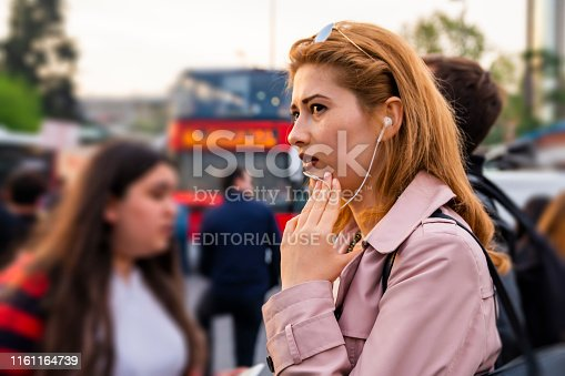 Istanbul, Turkey, 05/05/2019. Young business woman is standing in crowd street and talking on phone via headphone mic.