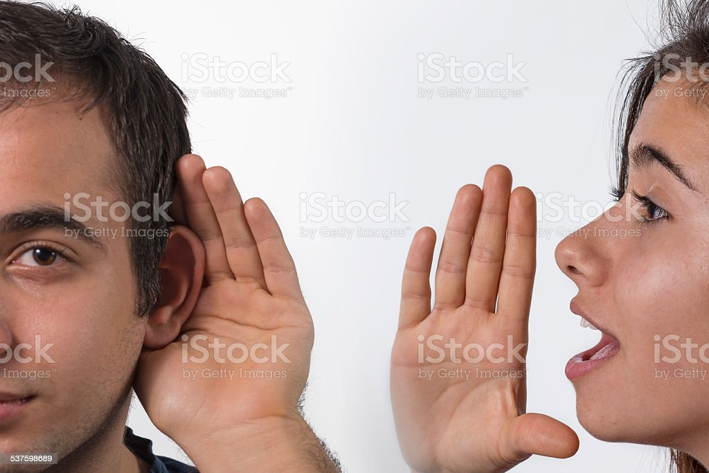 Yound girl whispering in man's ear stock photo